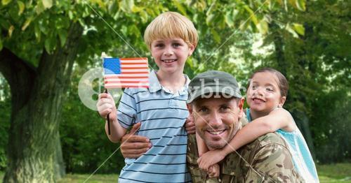 Portrait of father in soldier uniform with their kids at park