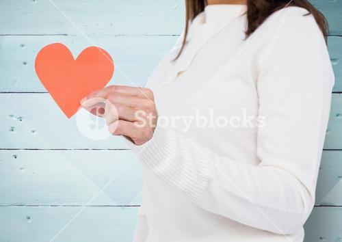 Mid-section of woman holding broken hearts