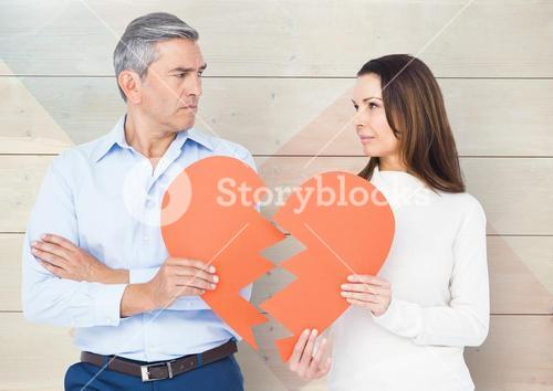 Sad couple looking each other while holding broken hearts
