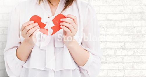 Mid-section of woman holding two broken hearts