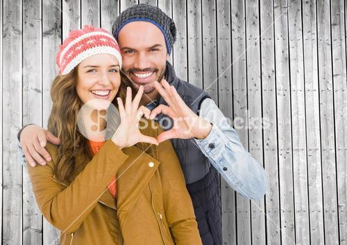 Portrait of happy couple forming a heart shape with hands