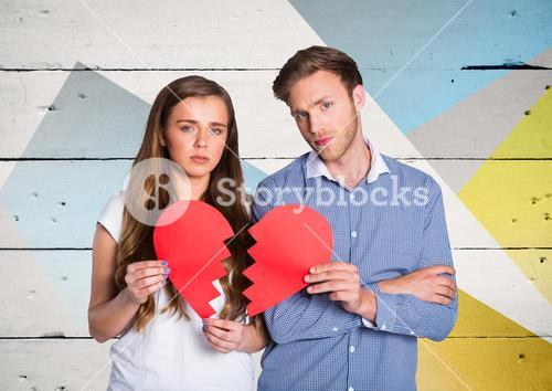 Portrait of sad couple holding broken hearts