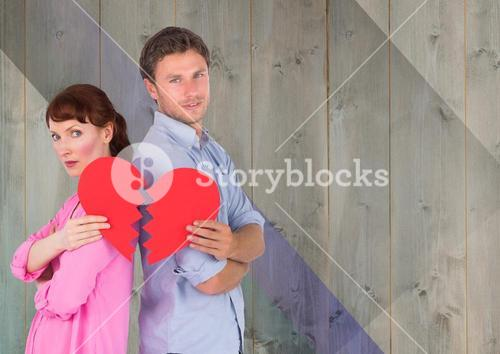 Couple standing back to back and holding broken hearts