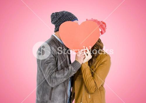 Couple hiding face behind orange heart