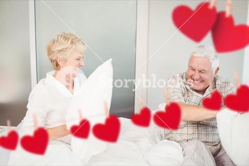 Senior couple having pillow fight in bedroom at home