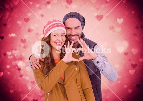 Happy couple making a heart symbol with hands