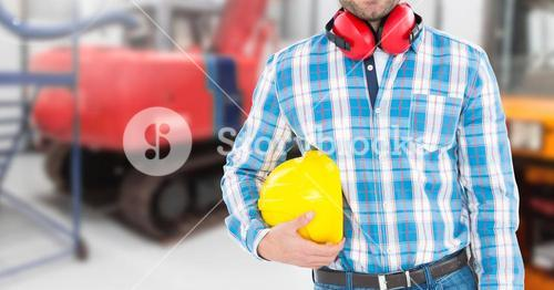 Engineer holding hardhat at construction site