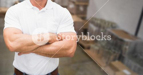 Mid section of supervisor standing with arms crossed