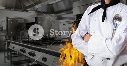 Mid section of chef standing with arms crossed in kitchen