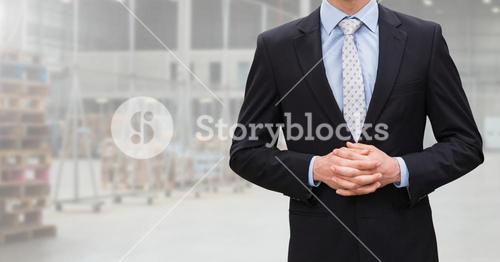 Mid section of businessman standing with hands clasped
