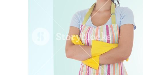 Female cleaner standing with arms crossed wearing apron and rubber gloves
