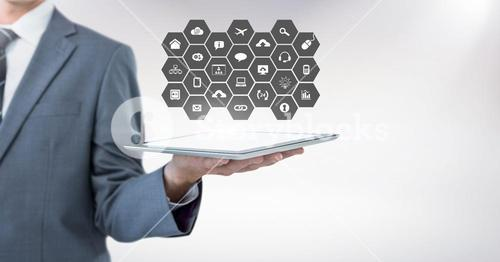 Mid section of businessman holding digital tablet with social media icon set