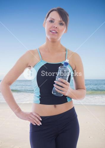 Portrait of fit woman standing with water bottle