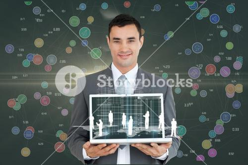 Portrait of smiling businessman holding laptop with graphics