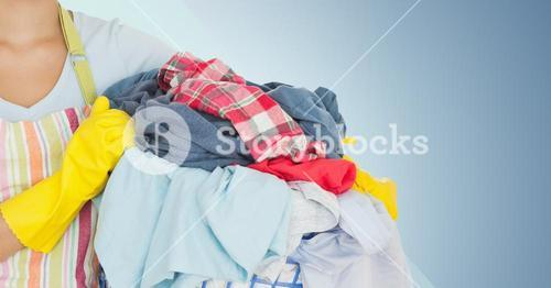 Mid section of female cleaner holding laundry basket filled with clothing