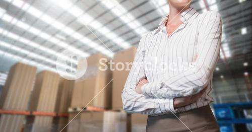 Mid section of businesswoman standing with arms crossed