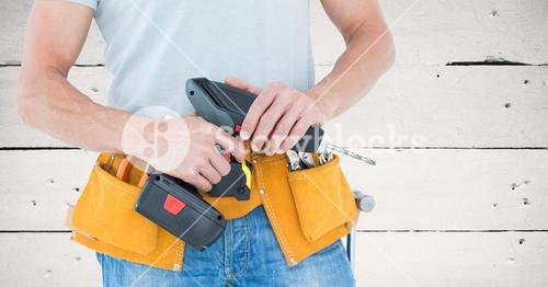 Mid section of handyman holding a drill machine with tool belt around waist