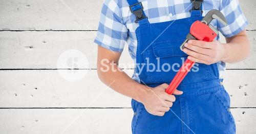 Mid section of handy man holding wrench