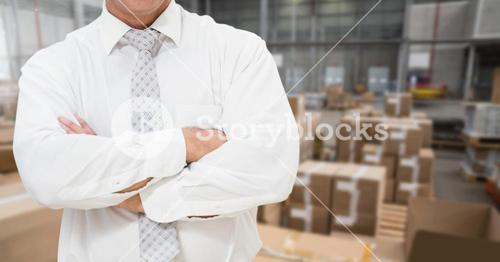 Businessman standing with arms crossed in warehouse