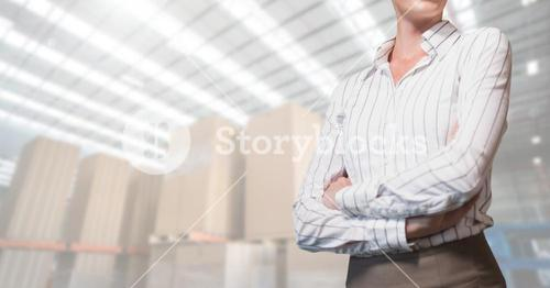 Businesswoman standing with arms crossed in warehouse