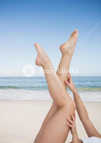 Woman touching her legs on the beach
