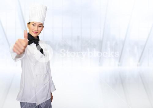 Portrait of smiling female chef cook showing thumbs up