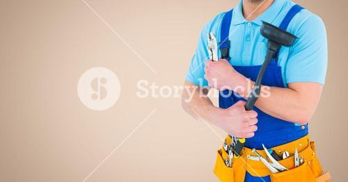 Mid section of handyman holding wrench and plunger with tool belt around his waist