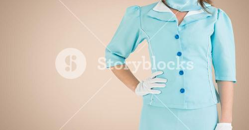 Air hostess standing with hands on hip against beige background