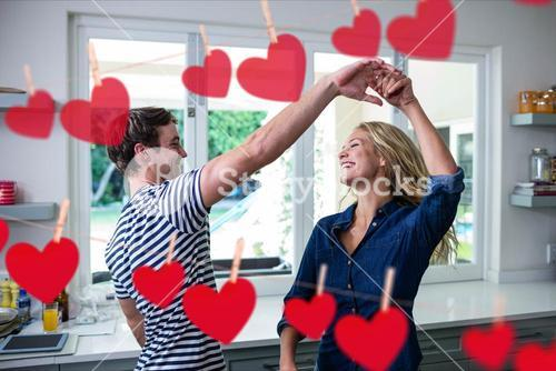 Composite image of red hanging hearts and couple dancing in the kitchen