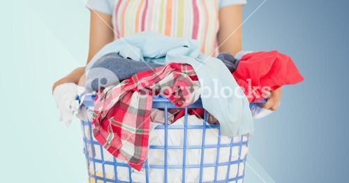 Mid section of female cleaner holding laundry