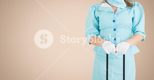 Air hostess holding luggage against beige background