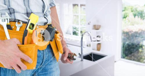 Handyman with tool belt at home