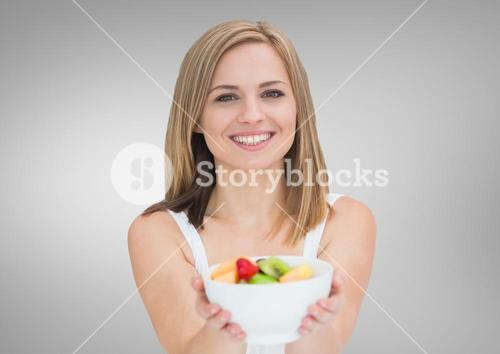 Portrait of beautiful woman holding fruit bowl