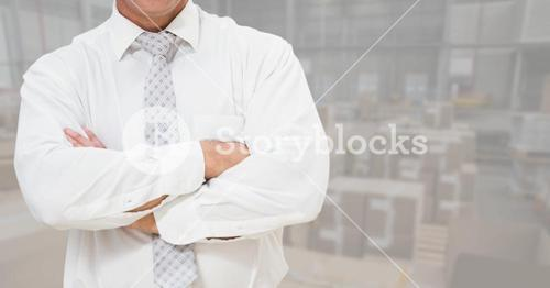 Businessman standing with arms crossed at warehouse