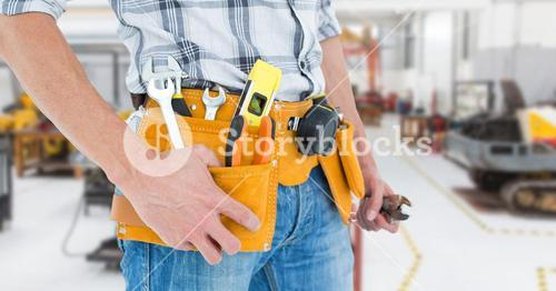 Handyman with tool belt at workshop