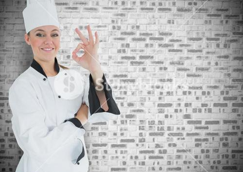 Happy female chef showing ok sign against brick wall