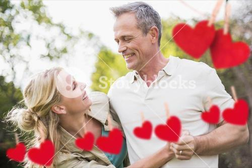 Couple having fun with red hanging hearts