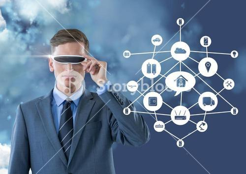 Business man wearing vr glasses standing next to digitally generated connecting icons