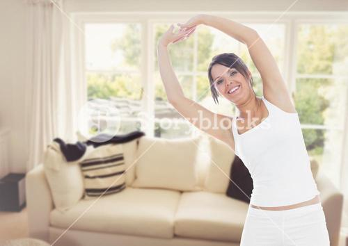 Beautiful woman performing stretching exercise in living room