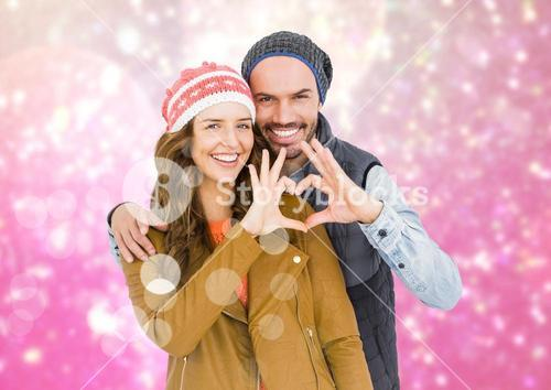Couple forming heart shape with hands against digitally generated background