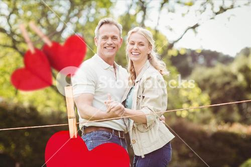 Composite image of hanging red hearts and couple embracing each other