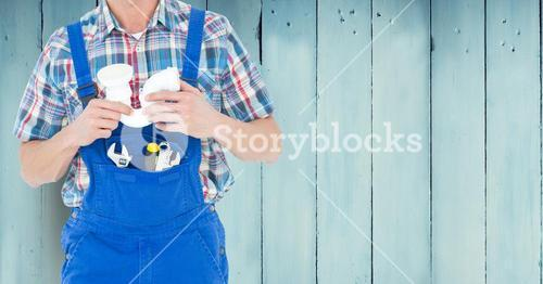 Handy man with tools standing against wooden background