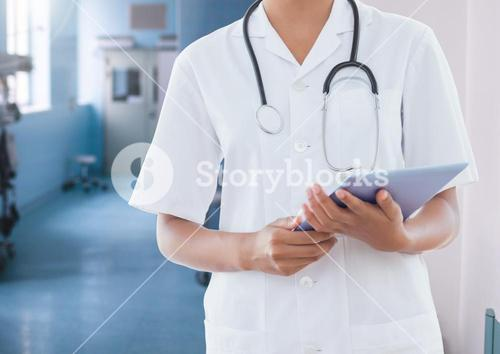 Mid section of doctor wih stethoscope and digital tablet