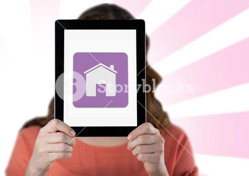 Woman holding digital tablet with home icon in front her face