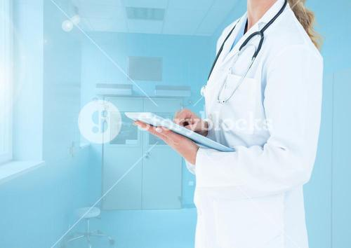 Mid section of female doctor using digital tablet