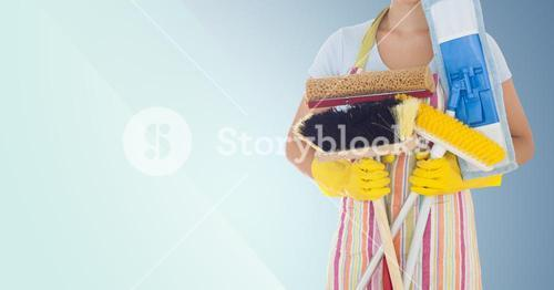 Mid-section of female cleaner holding brushes