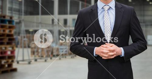 Businessman with hands clasped standing in warehouse
