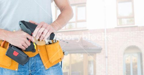 Mid-section of handy man with tool belt and drill