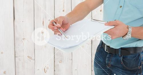 Delivery man holding a clipboard and pen against wooden background