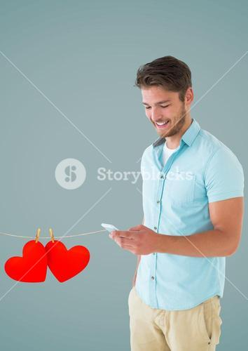 Composite image of smiling man texting and hanging red hearts